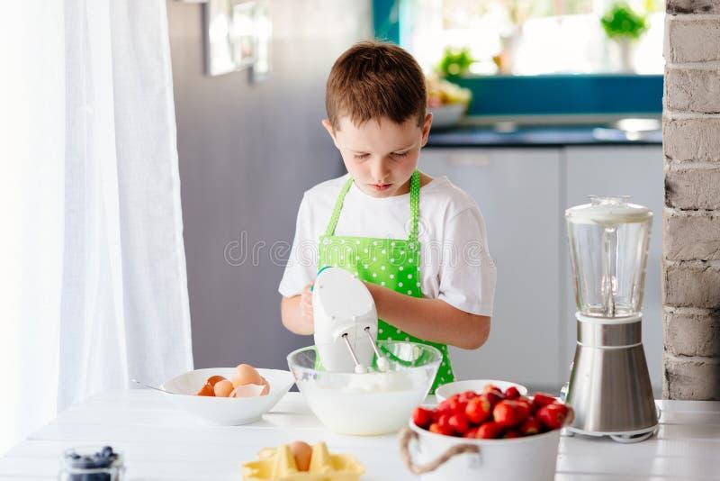 Mischender Teig des glücklichen Kinderjungen in der Glasschüssel stockfoto