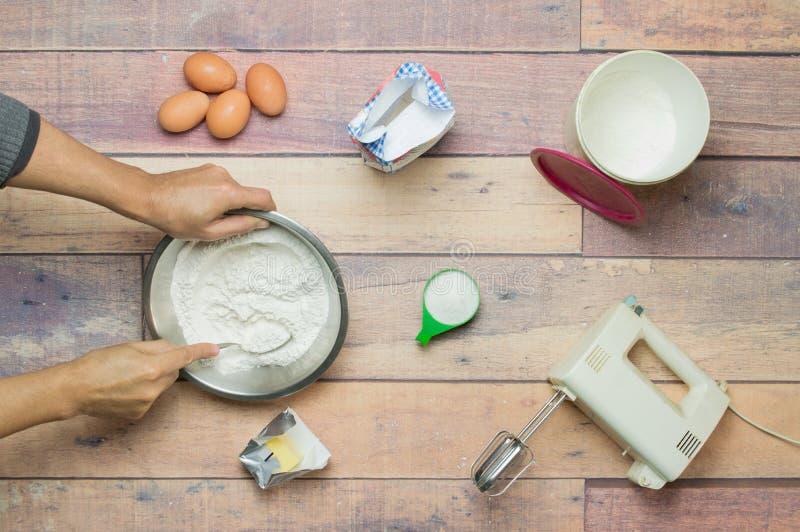 Mischendes Mehl, Eier, Butter und Zucker, zum eines Kuchens zu kochen stockbild