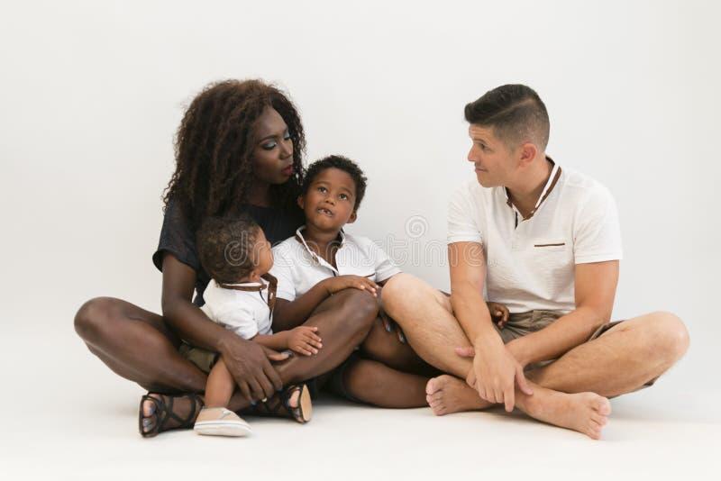 Mischerrennfamilie, die auf Boden mit 2 Kindern sitzt Lächelnder Coup stockfotografie