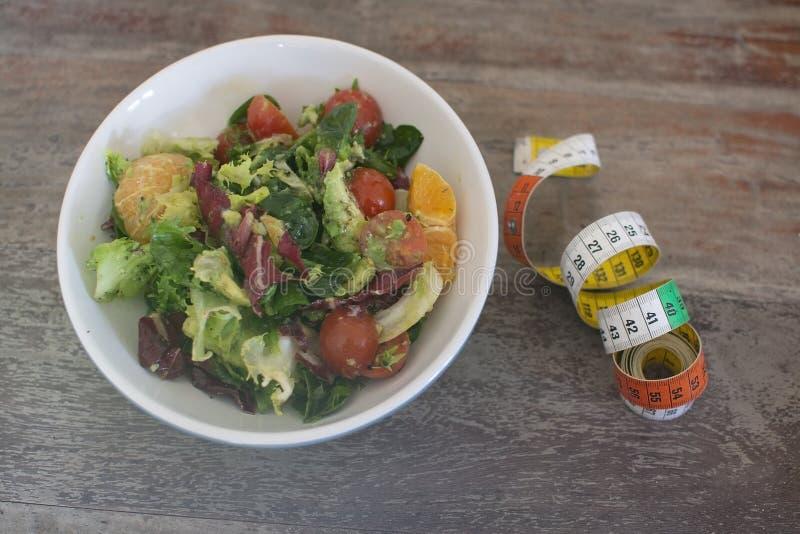 Mischgrün und purpurroter Salat mit messendem Band stockfotos