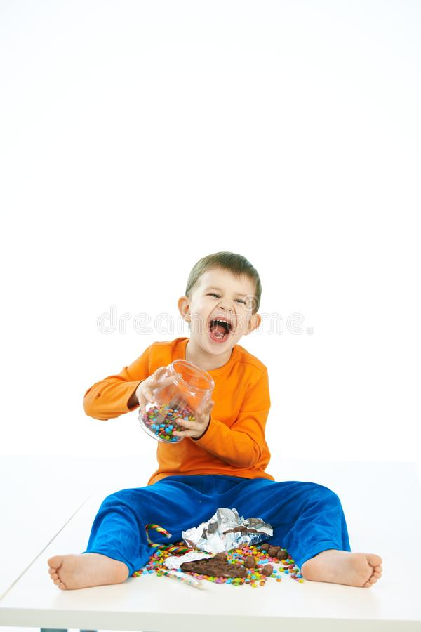 Mischievous boy with sweets jar sitting on floor. Mischievous little boy with sweets jar sitting on floor. Laughing, jar in hand, bare feet, isolated on white stock photography