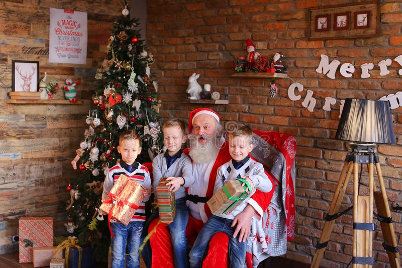 Native brothers boys sing Christmas carols to Santa Claus in roo. Mischievous and energetic male children kneel near Santa Claus, who sits on large soft armchair royalty free stock photo