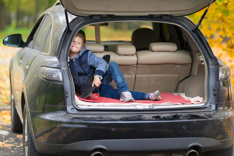 Mischievous little boy with a skateboard sitting in the trunk of a car grinning happily at the camera outdoors in a street in stock image