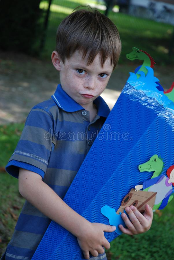 Mischievous looking boy with cornet with sweets in his hands stock image