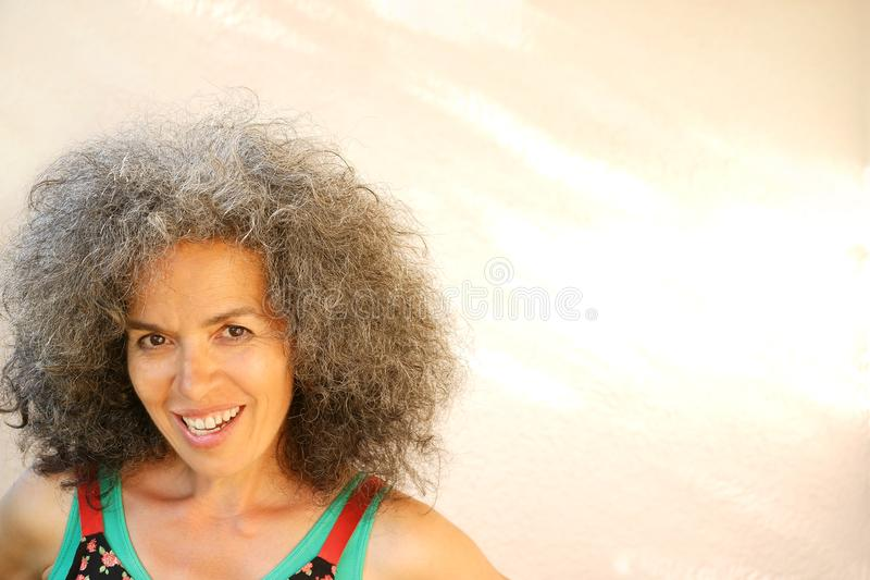 Mischievous smiling woman over 50 Curly graying hair. A smiling woman over fifty in summer clothing. Curly graying hair, Mediterranean type, headshot, open shade stock images