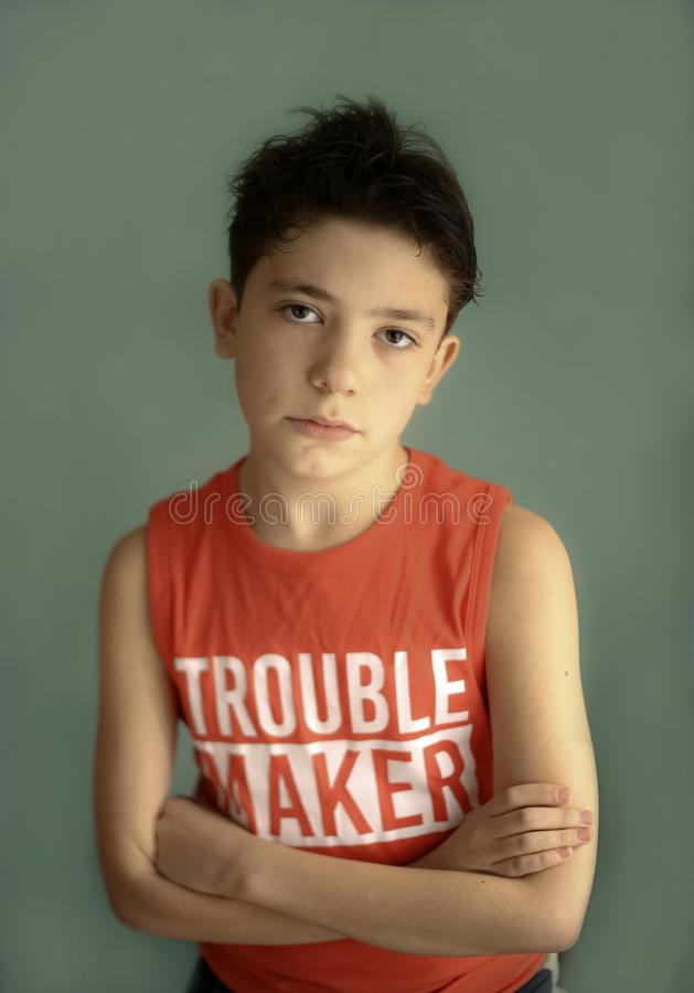 Mischievous teenager boy in trouble maker t-shirt close up sad portrait royalty free stock image