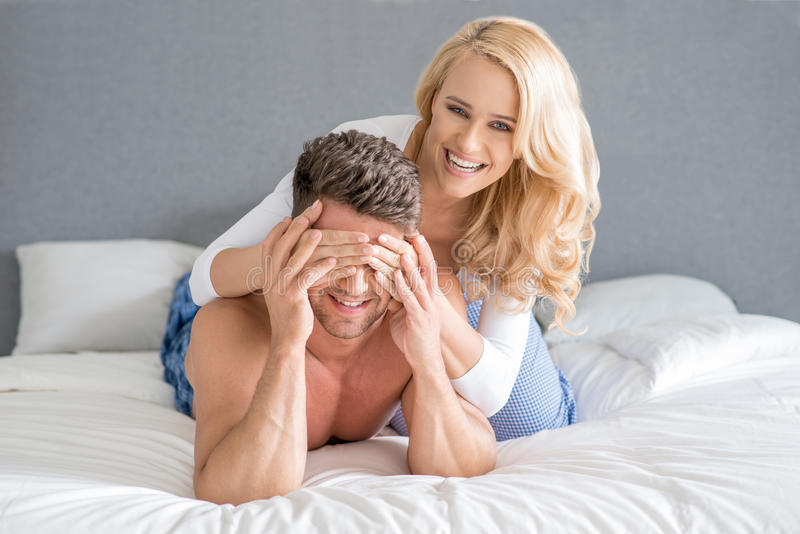 Mischievous woman covering her husbands eyes. Mischievous beautiful blond women covering her husbands eyes with her hands as they relax together on top of the stock photos