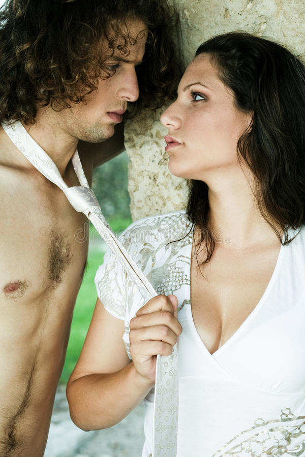 Mischievous young couple. Woman pulling male and being mischievous stock images