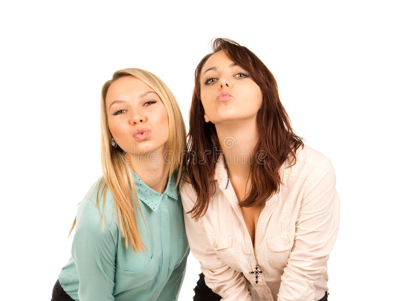 Mischievous young girls looking for a kiss. Two attractive mischievous young girls looking for a kiss standing close together pursing and puckering their lips royalty free stock image