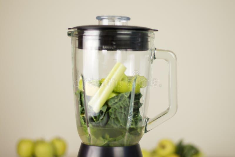 Mischmaschinenglas mit grünen Blättern, Sellerie und Äpfeln Früchte und veg stockbild