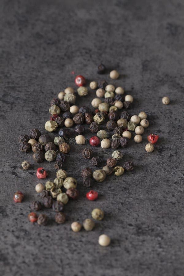 Mischpfefferkörner auf dunklem Hintergrund stockbilder