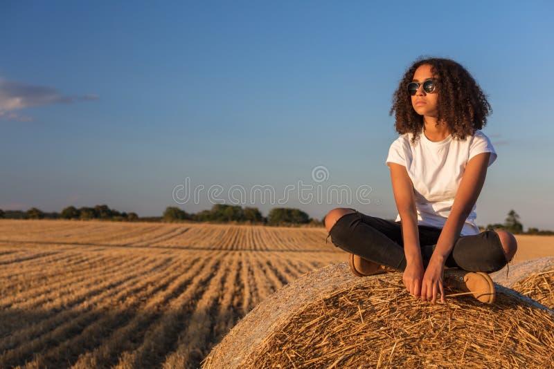 Mischrasse-Afroamerikaner-Mädchen-jugendlich Sonnenbrille, die auf Heu sitzt stockfoto