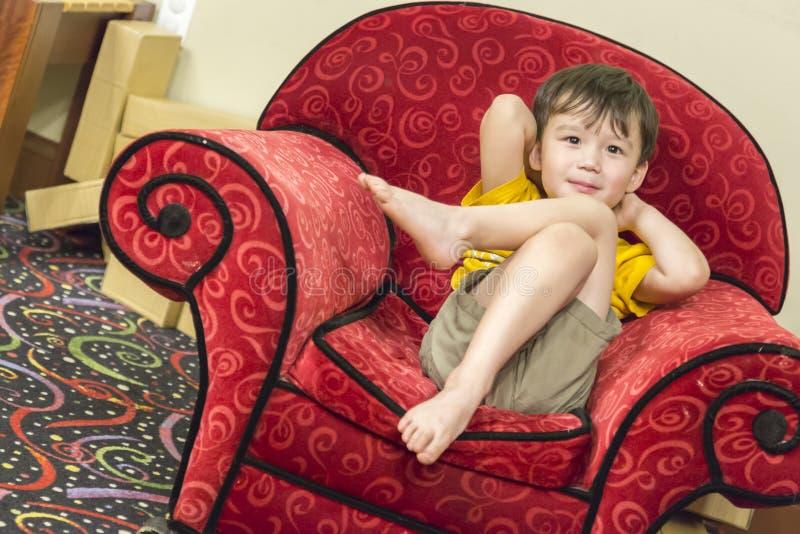 Mischrasse-Junge, der im bequemen roten Lehnsessel sich entspannt stockfotografie