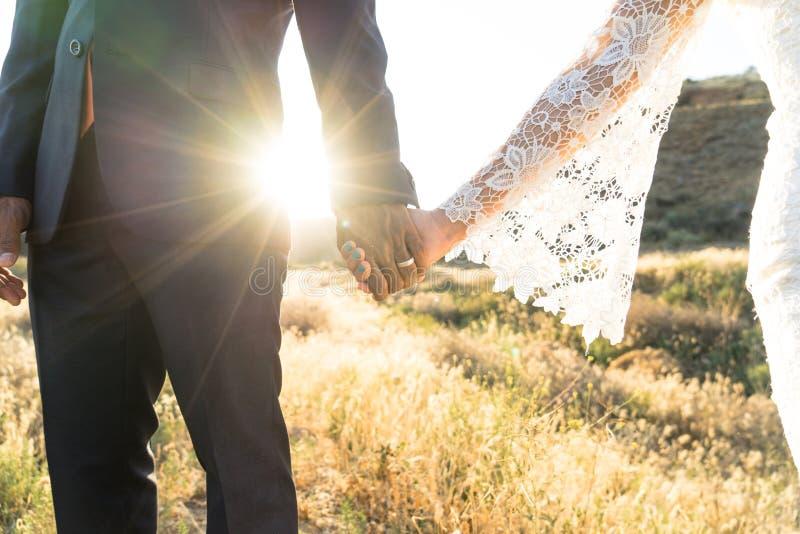 Mischrassebraut- und -bräutigamhändchenhalten bei Sonnenuntergang stockfotos