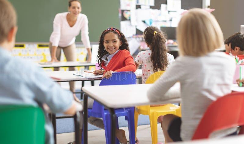 Mischrasseethnieschulmädchen, das auf einem blauen Stuhl betrachtet die Kamera in einem Klassenzimmer siiting ist lizenzfreie stockfotos