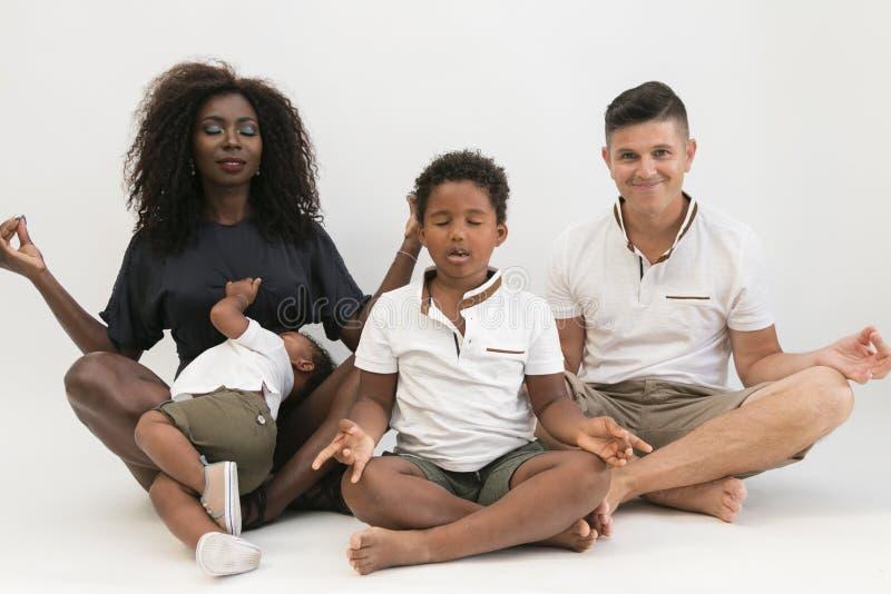 Mischrassefamilienmeditation, die mit Yoga sich entspannt Ausgeglichenes Leben c lizenzfreie stockbilder