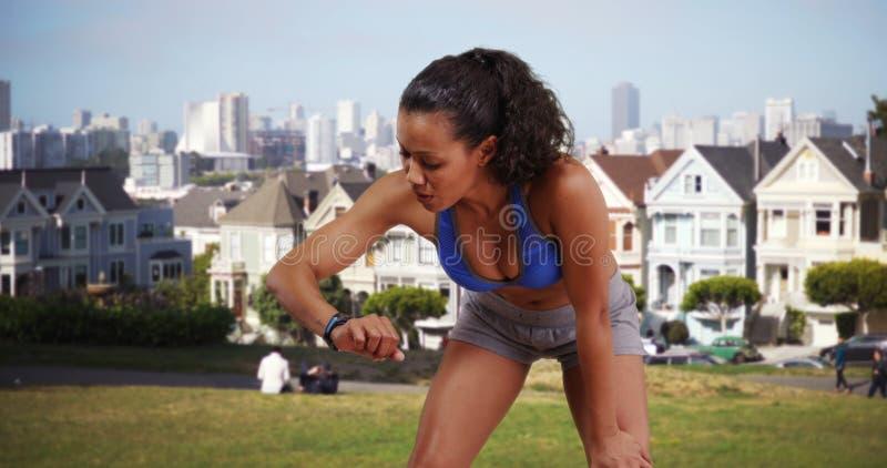 Mischrassefrauenläufer, der ihre Eignungsuhr auf den Park betrachtet stockbild