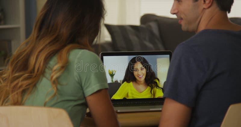 Mischrassefreunde, die online auf Laptop zu Hause sprechen stockbild