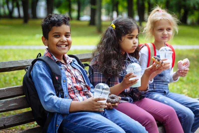 Mischrassengruppe Schulkinder, die zusammen das Mittagessen auf Bruch draußen nahe Schule essen Zur?ck zu Schule-Konzept lizenzfreie stockbilder