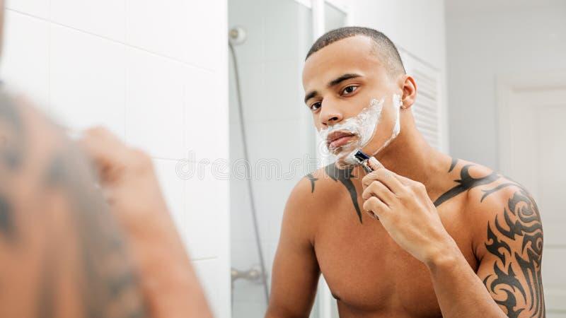 Mischrasseperson, die sein Gesicht rasiert stockfotos