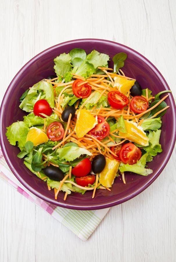Mischsalat mit Tomaten in der purpurroten Schüssel lizenzfreie stockbilder