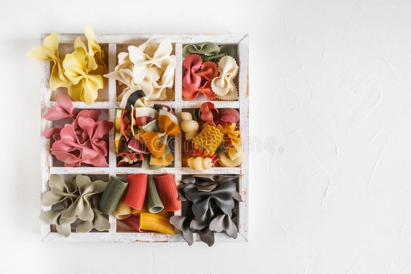 Mischsatz trockene mehrfarbige italienische Teigwaren auf einer weißen alten Holzkiste Hintergrund Abschluss oben lizenzfreie stockfotos