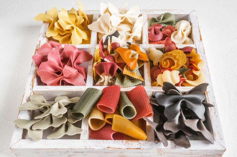 Mischsatz trockene mehrfarbige italienische Teigwaren auf einer weißen alten Holzkiste Hintergrund Abschluss oben stockfoto