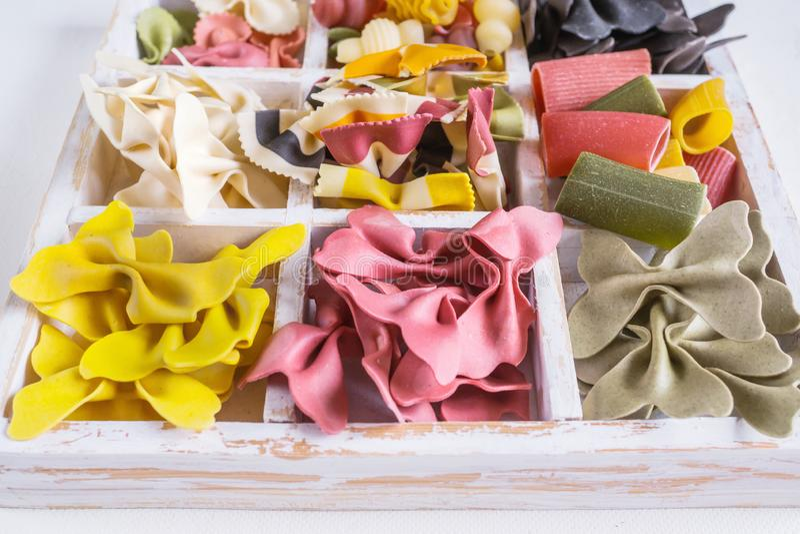 Mischsatz trockene mehrfarbige italienische Teigwaren auf einer weißen alten Holzkiste Hintergrund Abschluss oben stockbilder