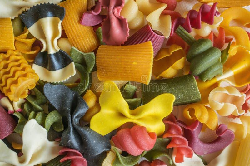 Mischsatz trockene mehrfarbige italienische Teigwaren auf einer weißen alten Holzkiste Hintergrund Abschluss oben lizenzfreie stockbilder