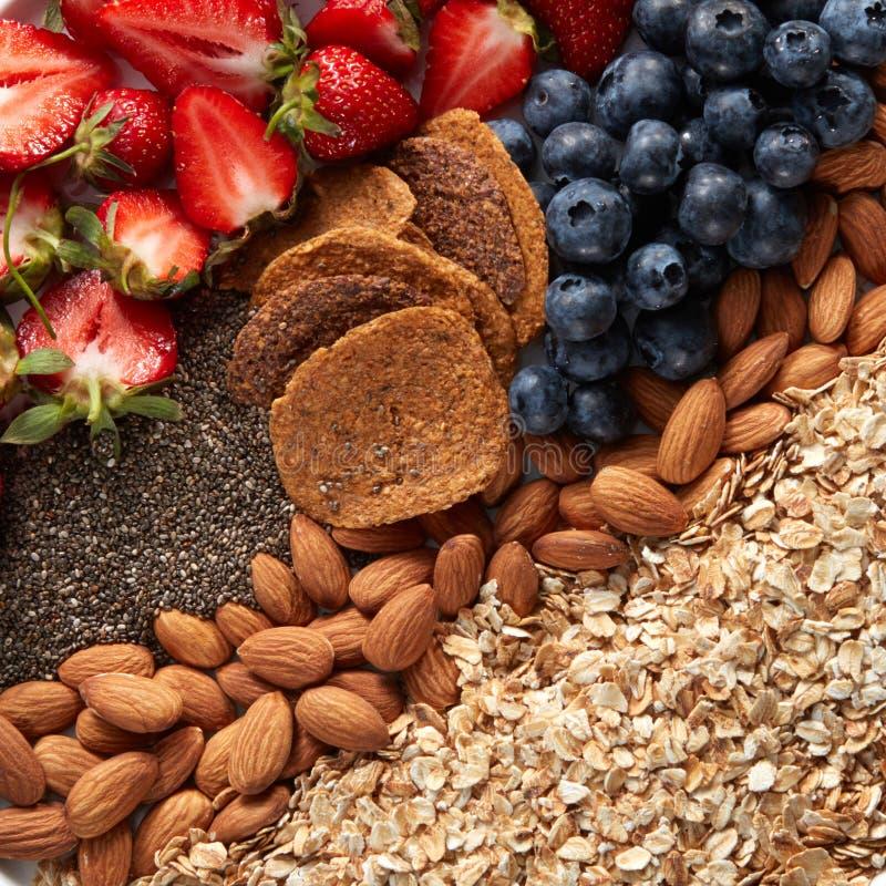 Mischung der Beeren-, Nuss-, Hafermehl- und Granolanahaufnahme Bestandteile für diätetische Nahrung stockfotos