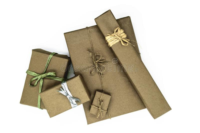 Mischung von den verschiedenen Größengeschenkboxen eingewickelt im beige Papier und mit verschiedenen Bändern auf weißem Hintergr stockfotografie