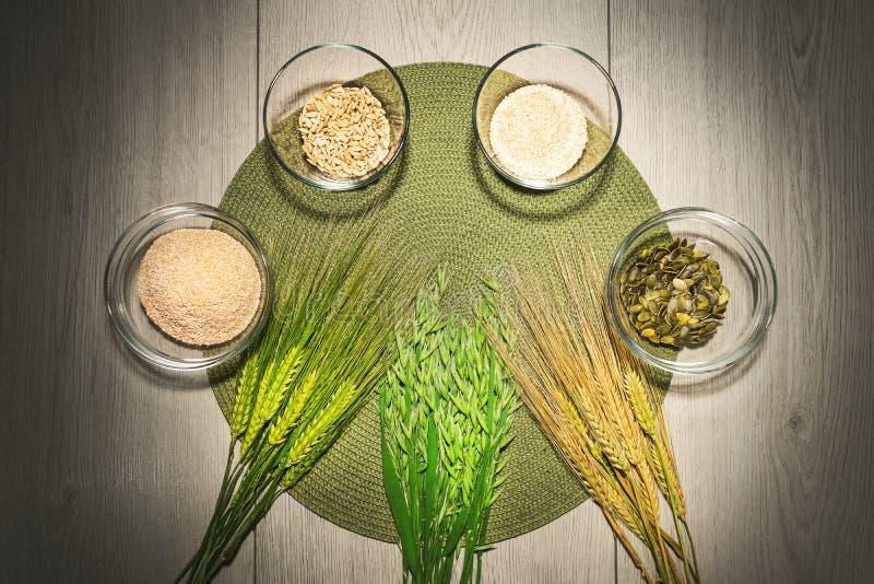 Mischung von verschiedenen Arten des Mehls in den Schüsseln mit frischen Weizen- und Gerstenkörnern stockfoto