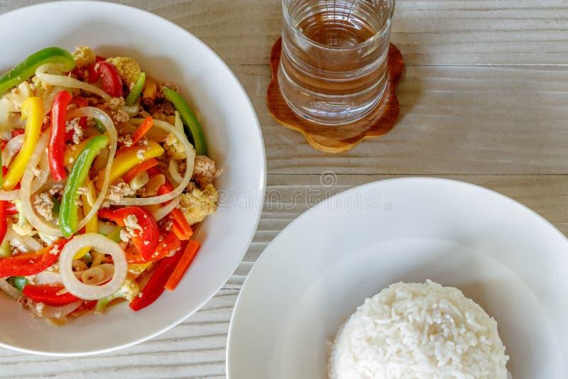 Mischungs-Pfeffer-Bonbon und gedämpfter Reis auf Holztisch, rührt Fried Pork mit Pfeffer-Bonbon stockfoto