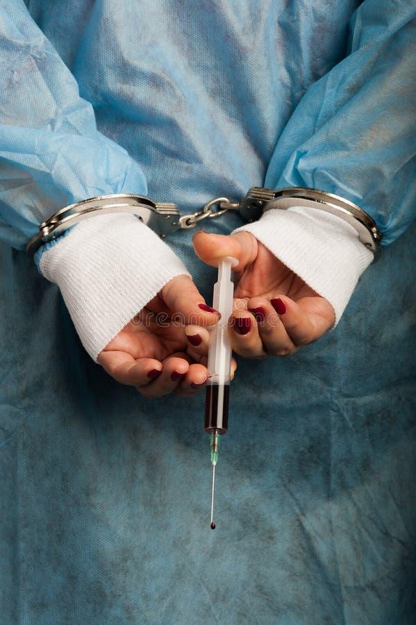 Misdadige de handboeien om:doen medische persoon met bloedige in hand injecteur stock fotografie
