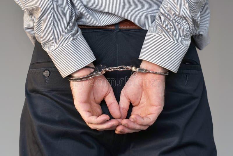 Misdadige handen die in handcuffs worden gesloten De mening van de close-up stock foto's