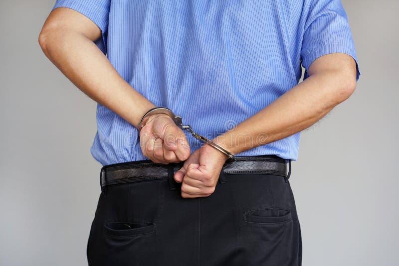 Misdadige handen die in handcuffs worden gesloten De mening van de close-up stock fotografie