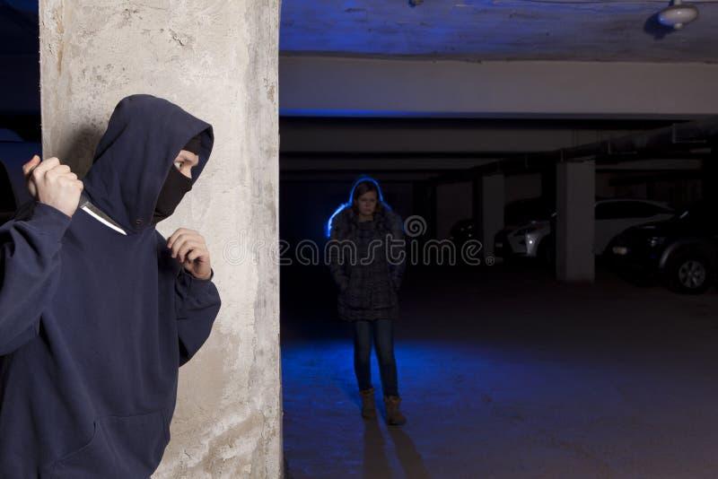 Misdadiger die met mes op een vrouw wachten stock afbeelding