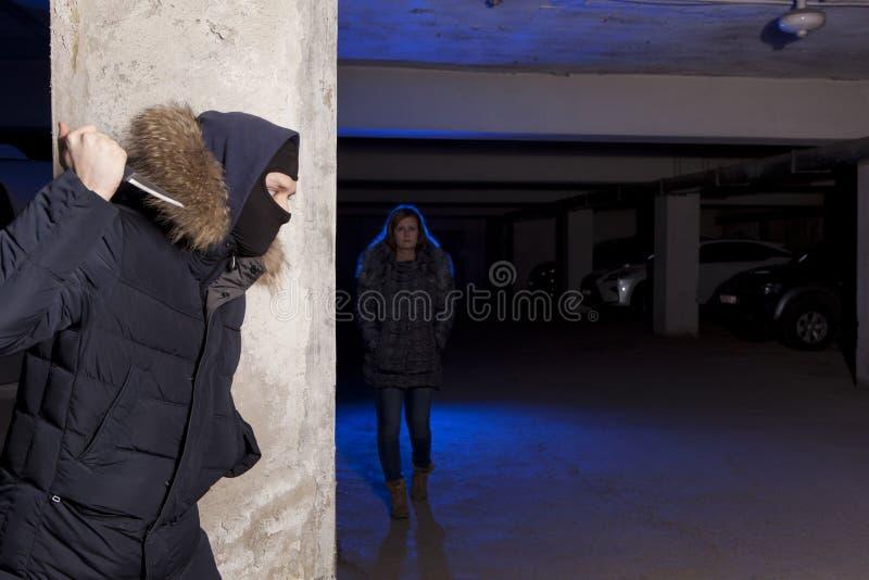 Misdadiger die met mes op een vrouw wachten stock fotografie