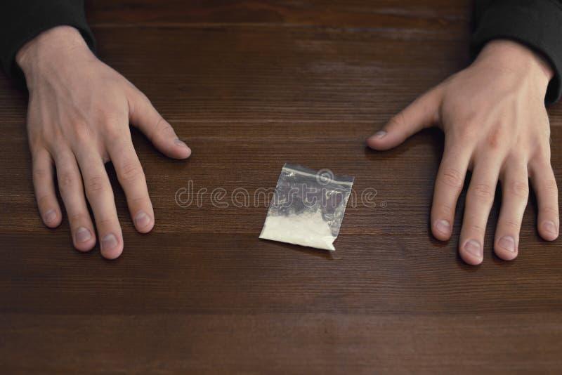 Misdadiger met drug bij houten lijst stock fotografie