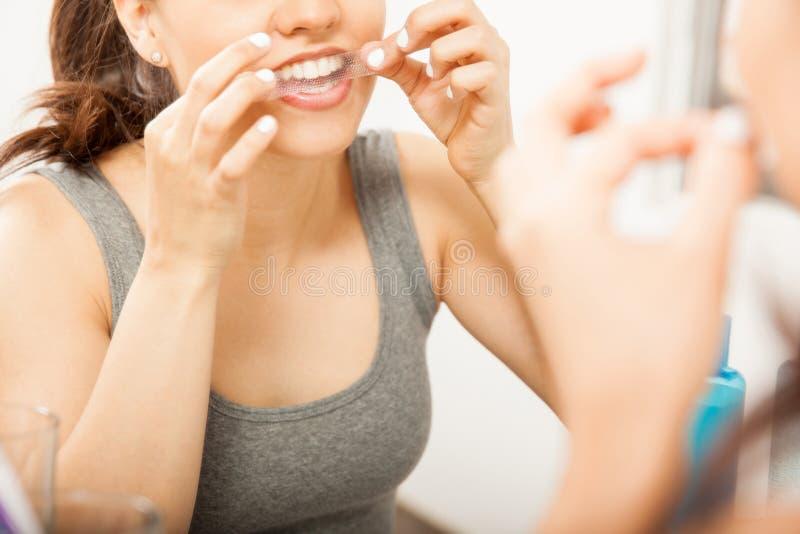 Mise d'une bande de blanchiment sur ses dents photos stock