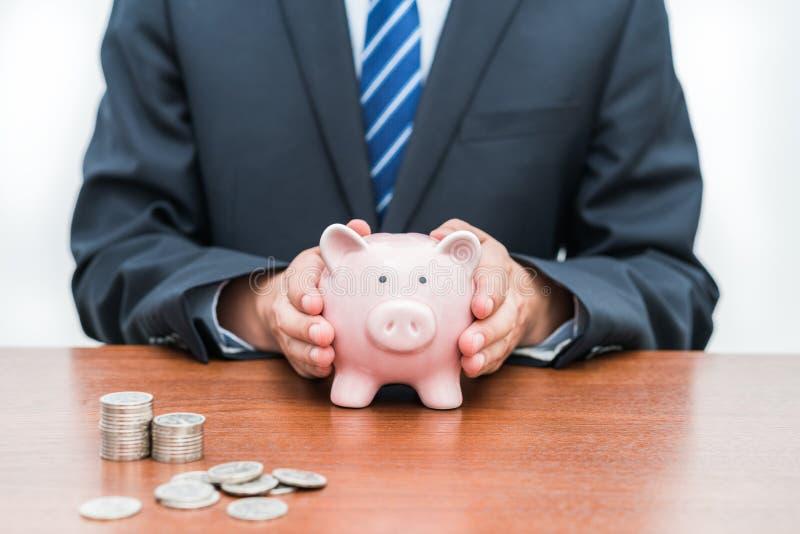 Mise des pièces de monnaie dans le concept porcin de banque-Le de l'épargne images libres de droits