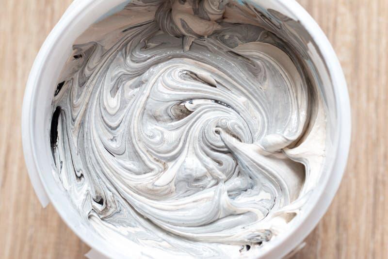 Mise texturisée mélangée à la peinture noire dans un récipient en plastique photo stock