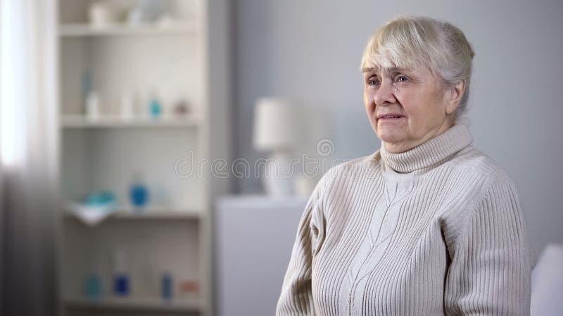Miserable elderly lady sitting alone in nursing house and crying, depression. Stock photo stock images