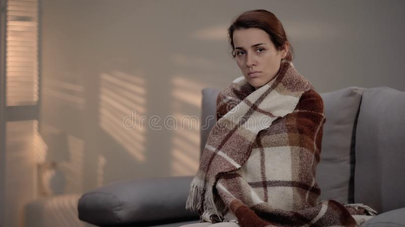 Miserable ill woman covered in plaid looking at camera, terminal disease, clinic. Stock photo stock images