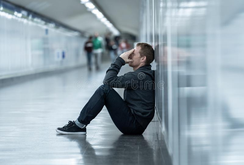 Miserable jobless young man crying Drug addict Homeless in depression stress sitting on ground street subway tunnel looking royalty free stock photo
