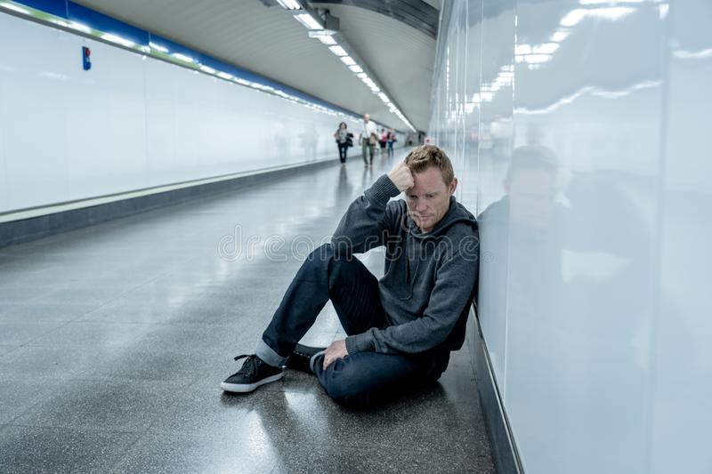 Miserable jobless young man crying Drug addict Homeless in depression stress sitting on ground street subway tunnel looking royalty free stock photos