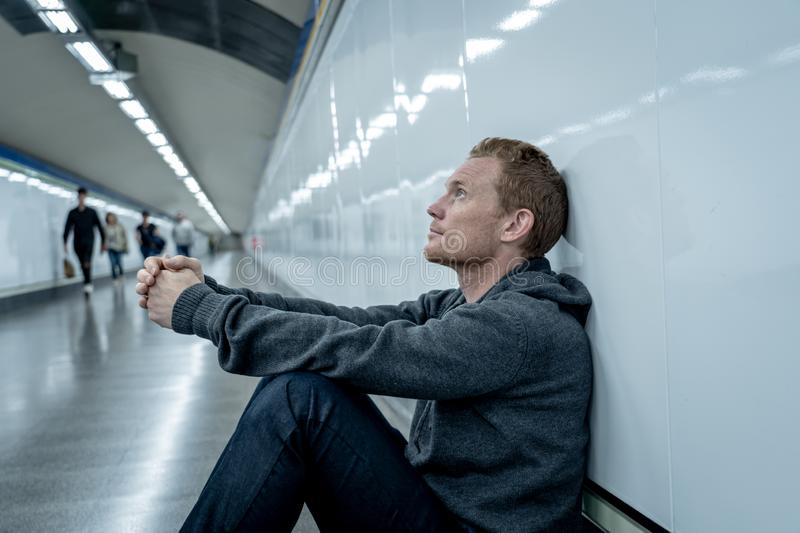 Miserable jobless young man crying Drug addict Homeless in depression stress sitting on ground street subway tunnel looking stock photos
