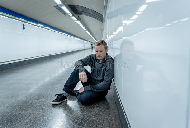 Miserable jobless young man crying Drug addict Homeless in depression stress sitting on ground street subway tunnel looking stock images