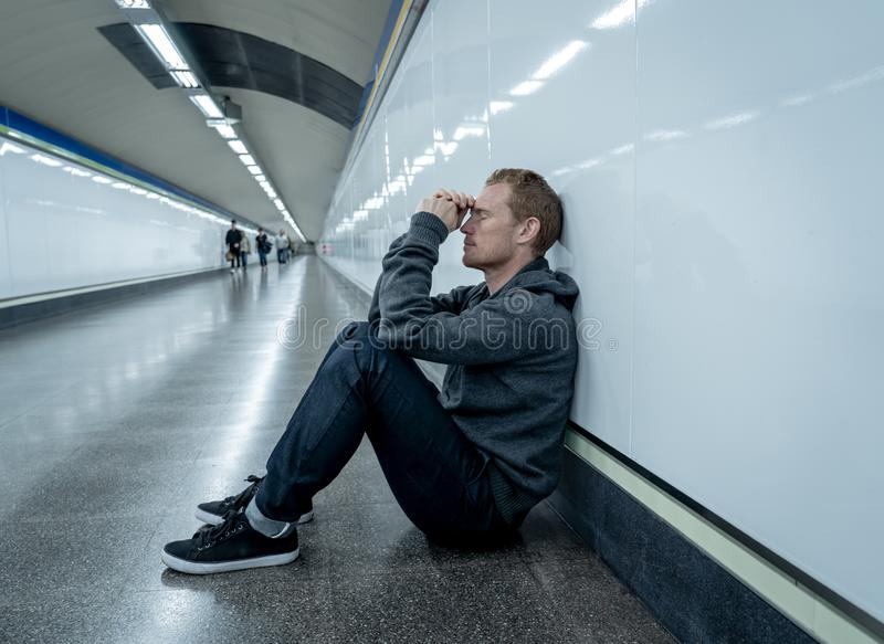 Miserable jobless young man crying Drug addict Homeless in depression stress sitting on ground street subway tunnel looking stock image
