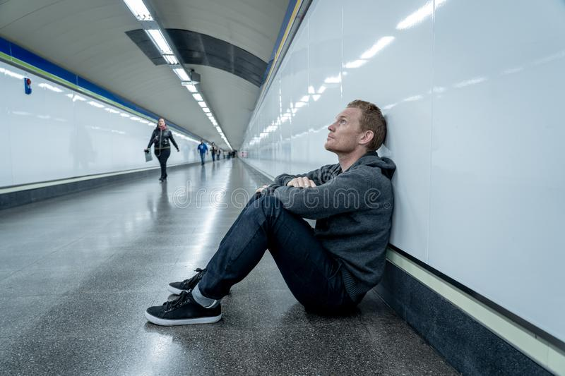 Miserable jobless young man crying Drug addict Homeless in depression stress sitting on ground street subway tunnel looking stock photography